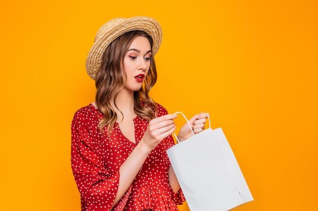 Geschokt verrast meisje dragen in een rode zomerjurk en strooien hoed met rode lippen kijkt in een boodschappentassen geïsoleerd over oranje muur Premium Foto