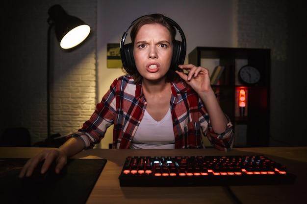 Geschokt vrouw gamer zittend aan tafel, online games spelen op een computer binnenshuis Premium Foto