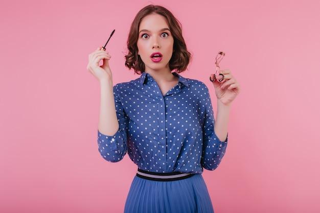 Geschokt vrouwelijk model in blauwe kledij poseren met mascara in de hand. mooie verbaasde vrouw krult haar wimpers. Gratis Foto
