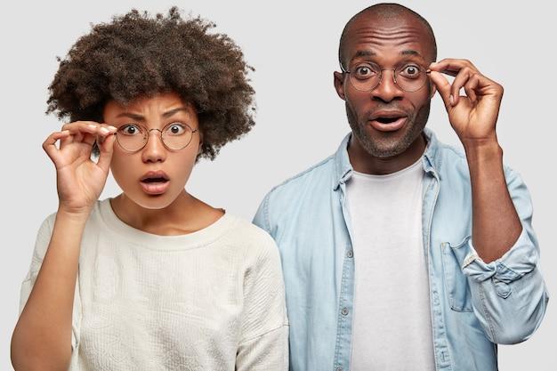 Geschokte afrikaanse amerikaanse vrouw en man met donkere huid, handen op de rand van een bril, verbaasd door verrassing voorbereid op hen, kan niet in iets geloven, poseren binnenshuis tegen witte muur Gratis Foto