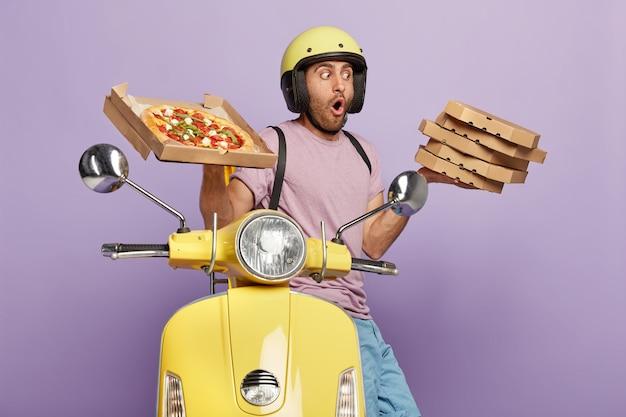 Geschokte bezorger draagt stapel heerlijke italiaanse pizza, draagt helm en vrijetijdskleding, rijdt motor, vervoert fastfood voor het avondeten, geïsoleerd over paarse muur. lekkere snack Gratis Foto
