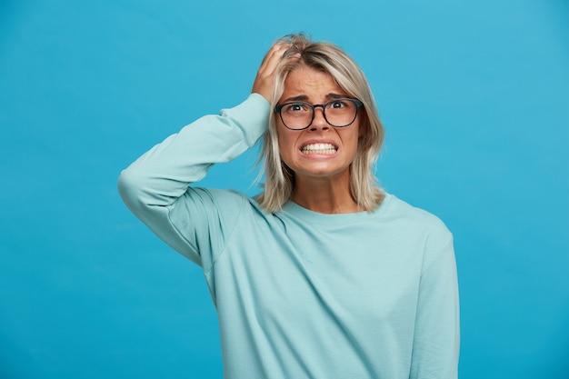 Geschokte blonde vrouw, ziet er bang uit voor de catastrofe, crash, ramp, van haar acties Gratis Foto