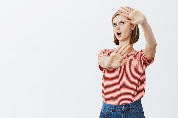 Geschokte en gekke jonge vrouw die verdedigend handen opheft en zichzelf beschermt Gratis Foto