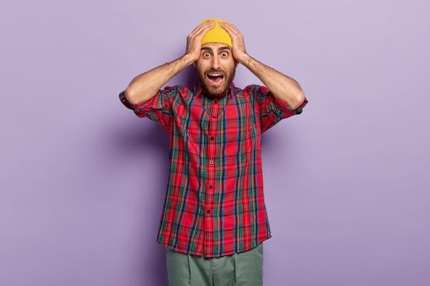 Geschokte europese man houdt de handen op het hoofd, gekleed in een gele hoed en een geruit overhemd, vraagt zich af zijn uitdrukking, poseert tegen een paarse achtergrond, bang voor iets vreselijks. bange man binnen Gratis Foto