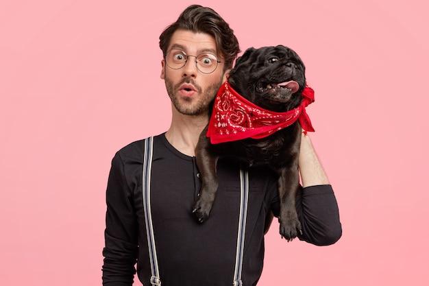 Geschokte hipster-man met verbaasde gezichtsuitdrukking, rashond op nek, bril en zwarte trui, poseert tegen roze muur, krijgt onverwacht nieuws van dierenarts. dieren Gratis Foto