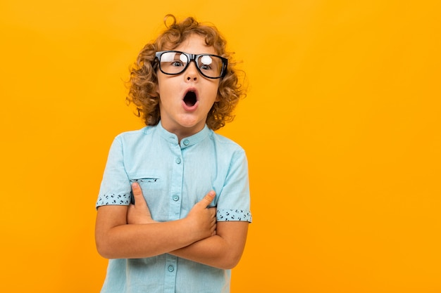 Geschokte krullende schooljongen met een bril op een geel Premium Foto