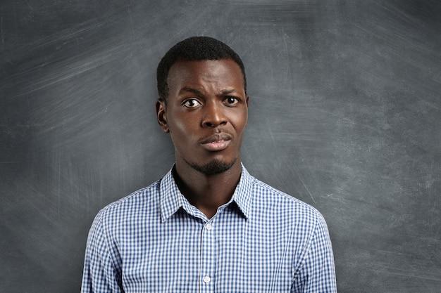 Geschokte leraar met een donkere huidskleur verrast met het wangedrag van zijn leerlingen tijdens zijn eerste schooldag. Gratis Foto