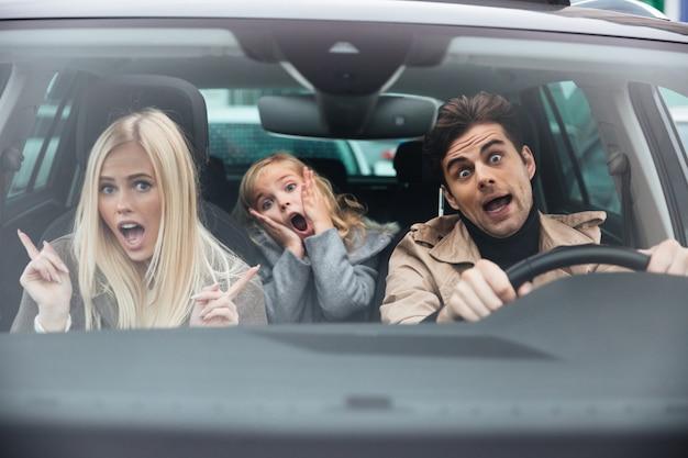 Geschokte man zit in de auto met zijn vrouw en dochter Gratis Foto