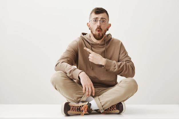Geschokte man zit op de vloer, wijst met de vinger naar links en kijkt bezorgd Gratis Foto