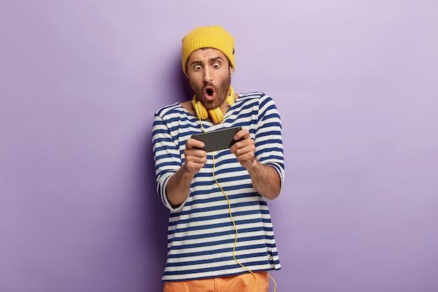 Geschokte ongeschoren man houdt mobiele telefoon horizontaal, houdt zijn adem in, speelt online games, is verslaafd, draagt een gele hoed en gestreepte trui Gratis Foto