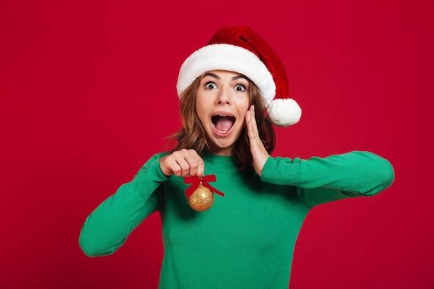 Geschokte opgewekte jonge dame die de hoed van kerstmissanta draagt Gratis Foto