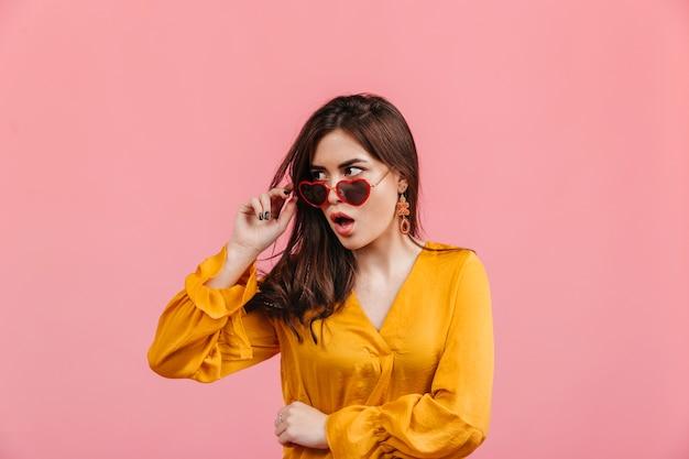 Geschokte stijlvolle dame zet haar hartvormige bril af. schot van donkerbruin meisje in lichte blouse op geïsoleerde roze muur. Gratis Foto