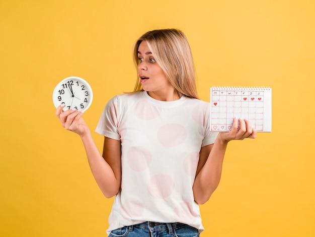 Geschokte vrouw die de klok bekijkt Gratis Foto