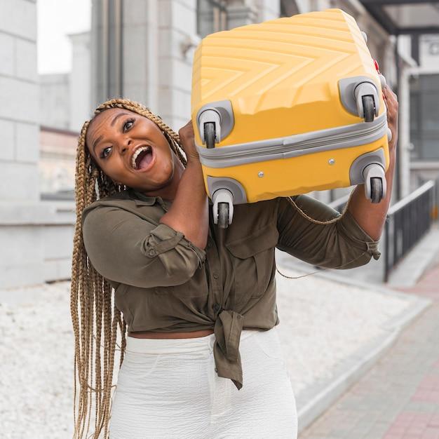 Geschokte vrouw die een zware bagage op haar schouder probeert op te tillen Gratis Foto