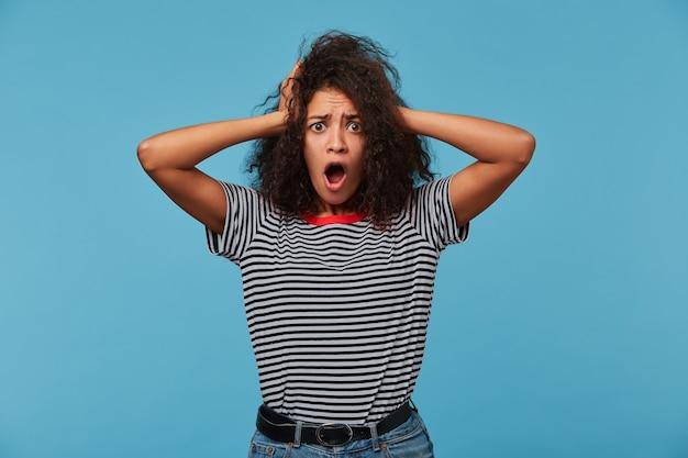 Geschokte vrouw staart naar voren en houdt haar mond open, krabt op haar hoofd en ziet er verrassend uit Gratis Foto