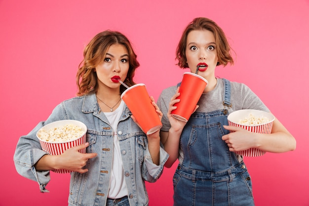 Geschokte vrouwen vrienden eten popcorn kijken film Gratis Foto