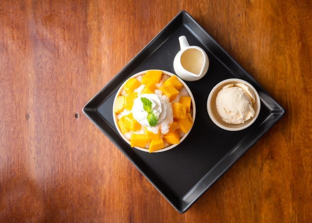 Geschoren ijsdessert met gesneden mango. geserveerd met vanille-ijs en slagroom. Premium Foto