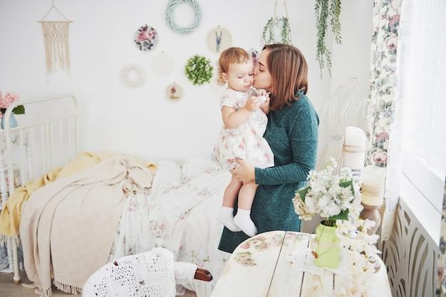 Geschoten van het gelukkige moeder spelen met haar baby in uitstekende kinderenruimte. het concept van gelukkige jeugd en moederliefde Premium Foto