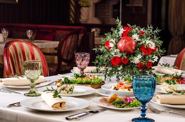 Geserveerd voor vakantie banket restaurant tafel met gerechten, snacks, salades, bestek, wijn en waterglazen. europees eten in een restaurant setting. tafel set voor een evenement feest. catering Premium Foto