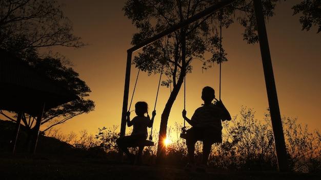 Gesilhouetteerde kinderenjongen en meisje die van mooie zonnige dag het spelen achtergrond genieten Premium Foto