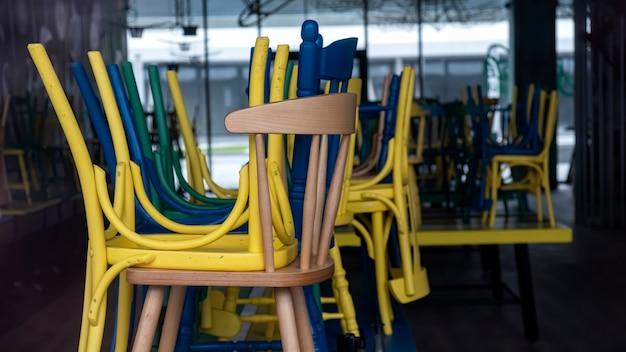 Gesloten café met verhoogde veelkleurige stoelen zichtbaar door de glazen gevel in boekarest, roemenië Gratis Foto