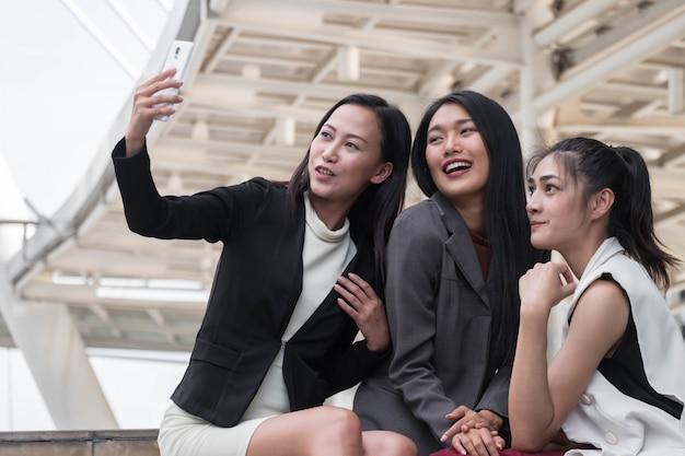 Gesloten omhoog jong vrouwen commercieel team dat in openlucht het nemen van een selfie plaatst Premium Foto