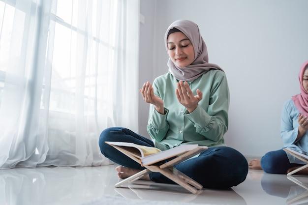 Gesluierde jonge vrouwen die samen bidden Premium Foto