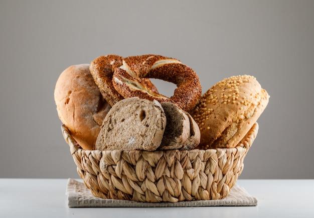 Gesneden brood met turks bagel zijaanzicht op een witte en grijze oppervlakte Gratis Foto