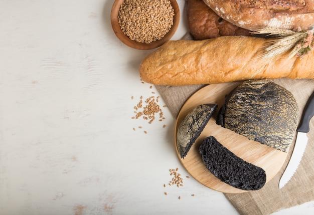 Gesneden brood met verschillende soorten vers gebakken brood op een witte houten achtergrond. bovenaanzicht, kopie ruimte. Premium Foto