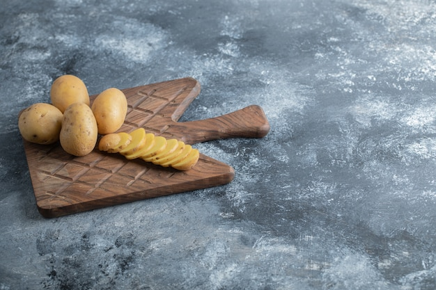 Gesneden en hele aardappelen op de houten snijplank. hoge kwaliteit foto Gratis Foto