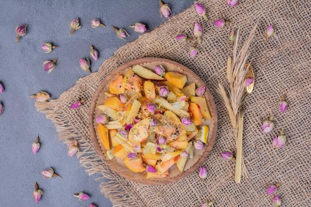 Gesneden fruitschaal met bloemen en doek op blauw. Gratis Foto