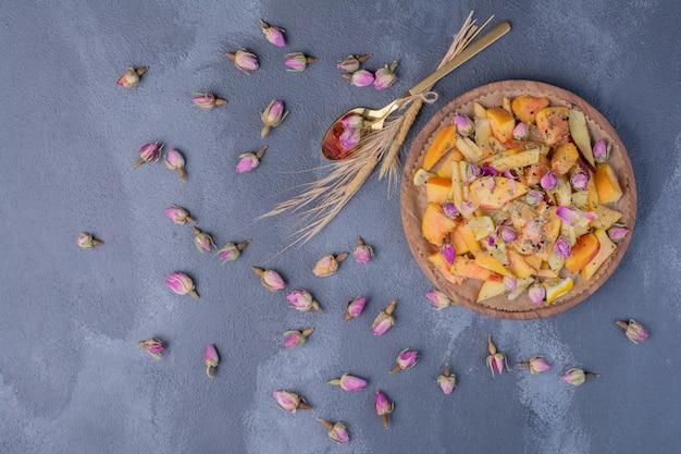 Gesneden fruitschaal met bloemen op blauw. Gratis Foto