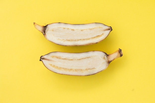 Gesneden gele banaan op geel achtergrond Premium Foto