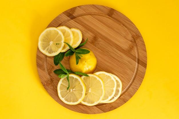 Gesneden gele citroenen op een bruin houten bord, ernaast ligt een bosje groene munt, zomerdranken Premium Foto