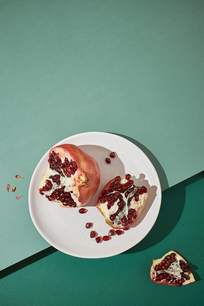 Gesneden granaatappel op een plaat op een groene achtergrond. leg plat en kopieer de ruimte Premium Foto