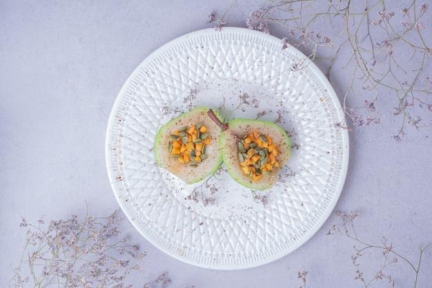 Gesneden peren met gehakte wortel en zaden in een witte plaat Gratis Foto