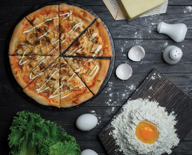 Gesneden pizza met ranchsaus en deeg maken met bloem en eieren Gratis Foto