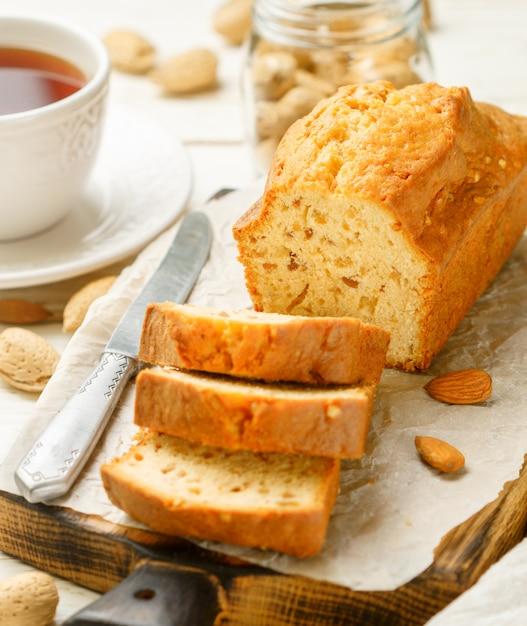 Gesneden pondcake met amandelen op de snijplank. zelfgemaakte cake met noten en honing Premium Foto