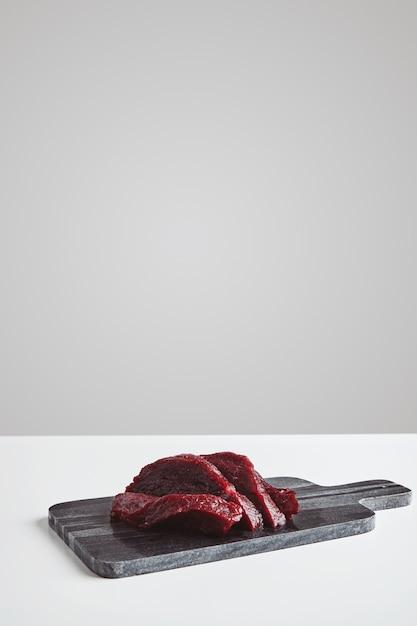Gesneden premie rauw walvisvlees steak op marmeren stenen snijplank geïsoleerd op een witte tafel Gratis Foto