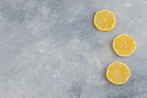 Gesneden sappige verse citroenen geplaatst op marmeren achtergrond. Gratis Foto