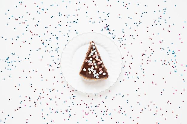 Gesneden verjaardagstaart met confetti Gratis Foto