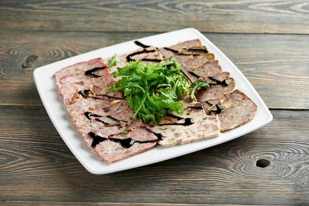 Gesneden vlees plaat versierd met greens en saus op de houten tafel in het plaatselijke restaurant copyspace eten voorgerecht gebakken delicatesse gastronomische hongerige eetlust concept. Gratis Foto