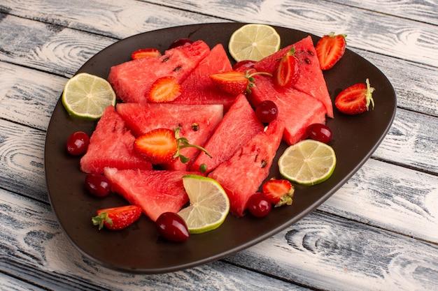 Gesneden watermeloen met citroenaardbeien in bruine plaat op grijs Gratis Foto