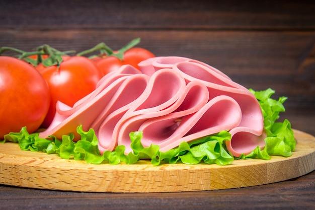 Gesneden worst met salade op een ronde houten bord. Premium Foto