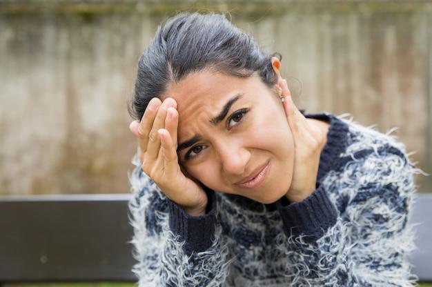 Gespannen mooie vrouw hoofd aan te raken buitenshuis Gratis Foto