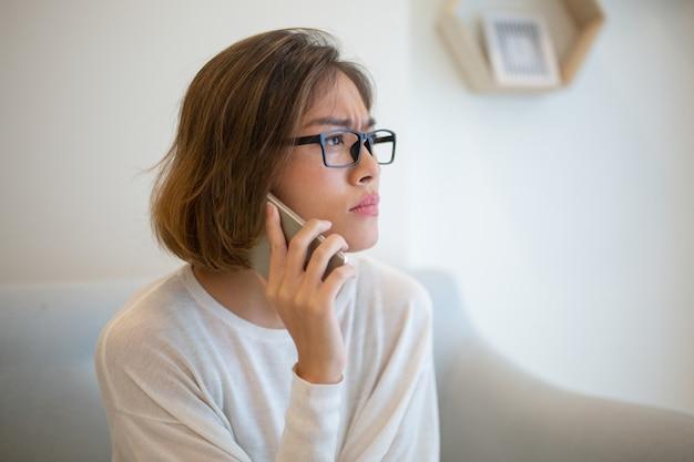 Gespannen vrouw die smartphone op bank thuis uitnodigen Gratis Foto