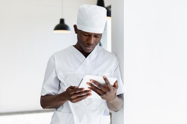 Gespecialiseerde mannelijke arts met behulp van een digitale tablet Gratis Foto