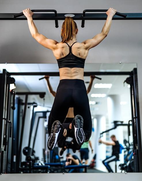 Gespierd, atletisch meisje, bodybuilder in sportkleding omhoog te trekken op een rekstok voor de spiegel bij sportschool. Premium Foto