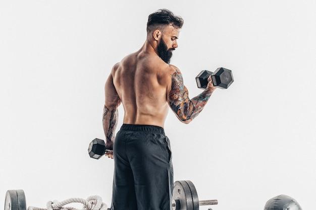 Gespierde atleet bodybuilder man met een naakte torso training met halter. Premium Foto
