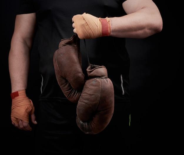 Gespierde atleet in een zwart uniform heeft zeer oude bruine bokshandschoenen in zijn hand Premium Foto